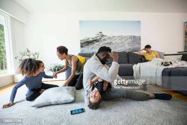 playfighting in the family living room - girl wrestling stock pictures, royalty-free photos & images