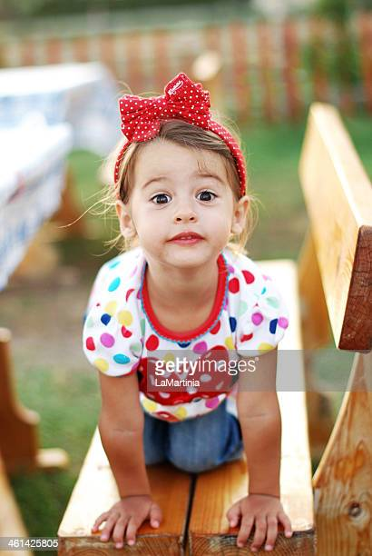 Playful 2 year old girl on a bench