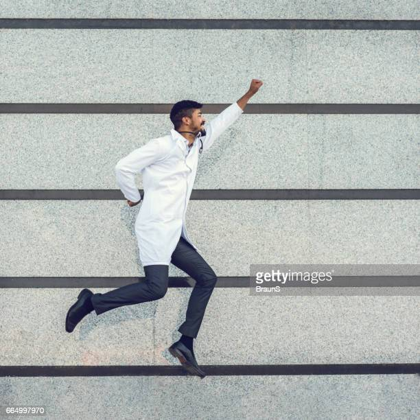 Playful African American doctor flying against the wall.