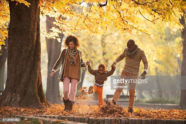 Playful African American family walking in autumn park.