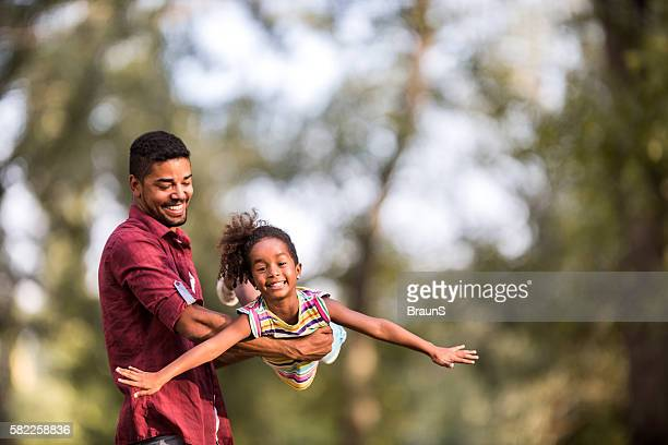 Playful African American father and daughter in nature.