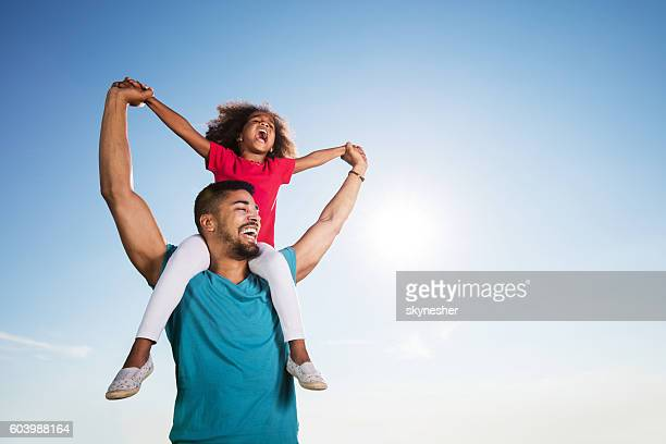 Playful African American father and daughter laughing against the sky.