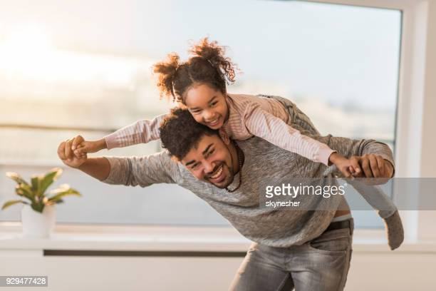 Playful African American father and daughter piggybacking at home.
