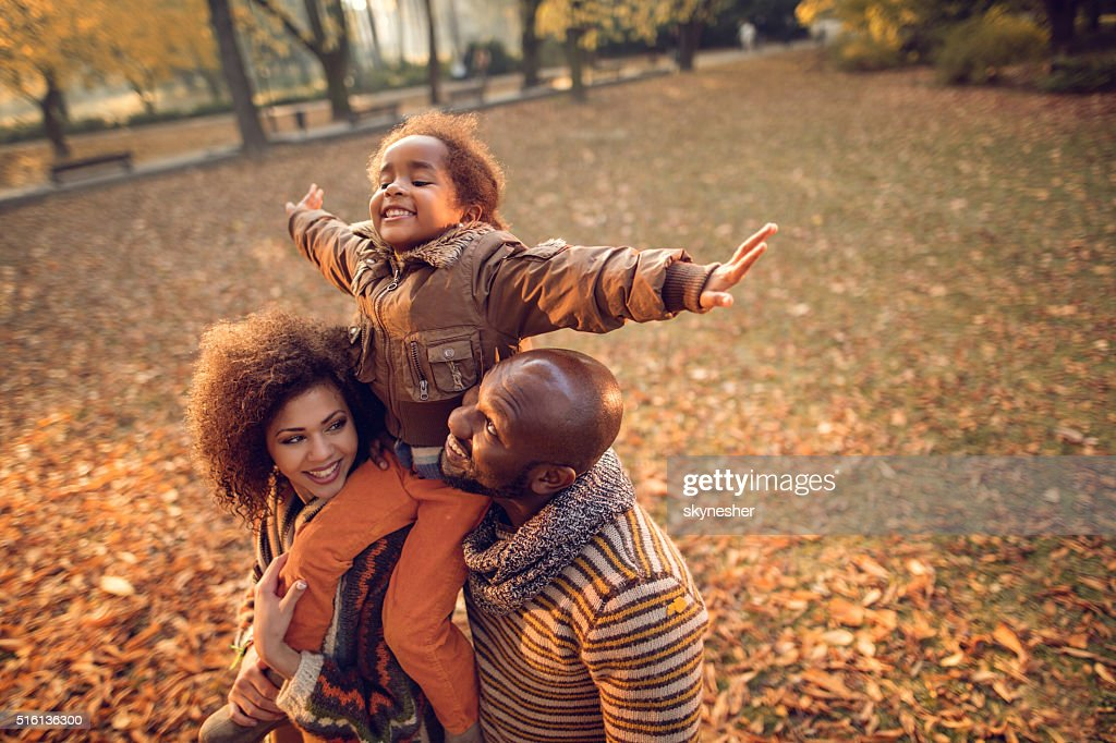 Playful African American little girl having fun with parents outdoors. : Stock Photo