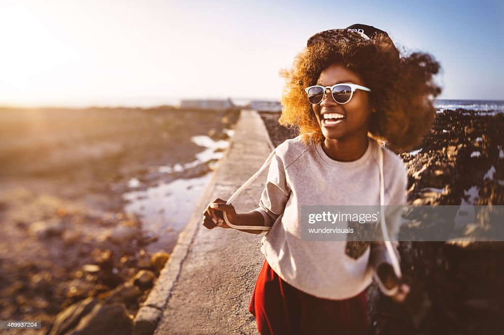 Playful African American teen hipster at the beach : Stock Photo