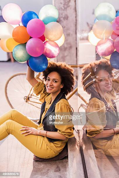 Playful African American woman holding colorful balloons.