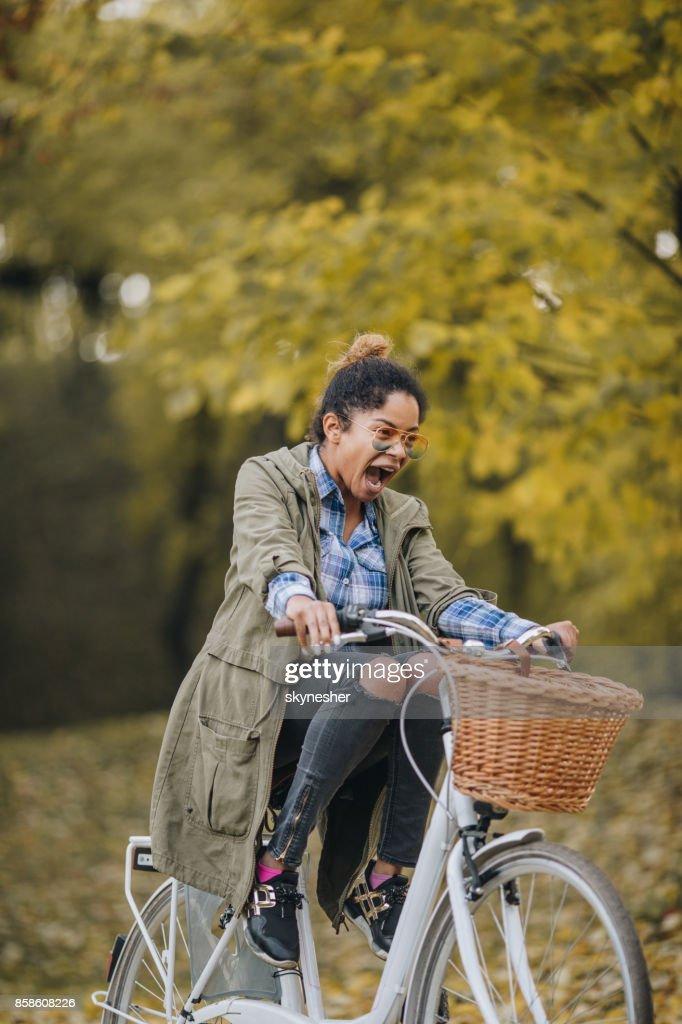 Spielerische afroamerikanische Frau, Fahrrad fahren und schreien. : Stock-Foto
