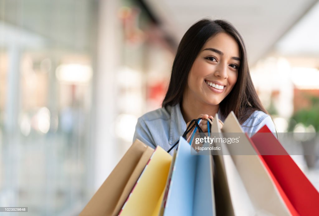 Playful and excited young woman at the mall in a shopping spree looking at camera smiling : Stock Photo