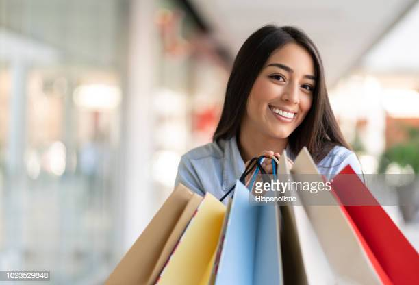 Playful and excited young woman at the mall in a shopping spree looking at camera smiling