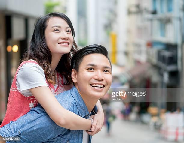 Playful Asian couple having fun in the street