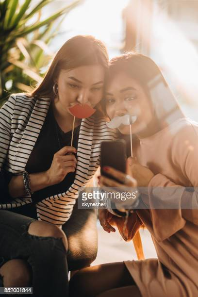 Playful Asian women having fun while taking a selfie with cell phone.