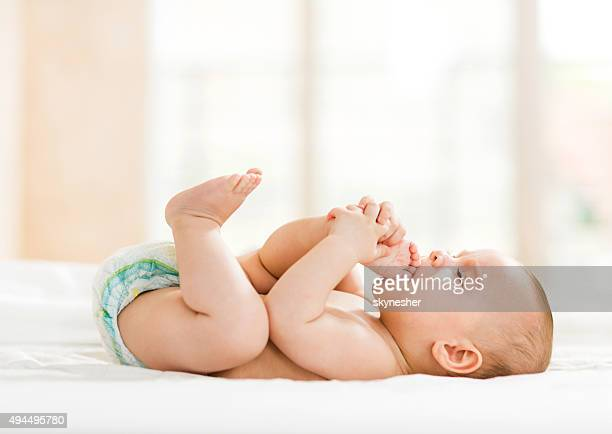 Playful baby lying down in bed.
