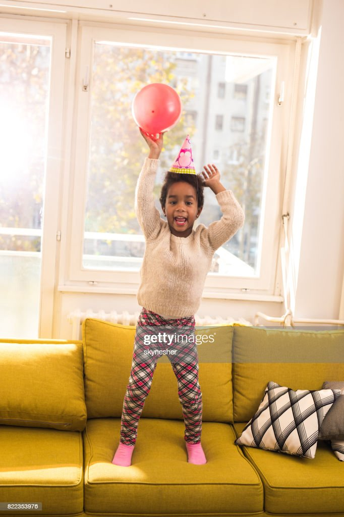 Playful black girl having fun on a party at home. : Stock Photo
