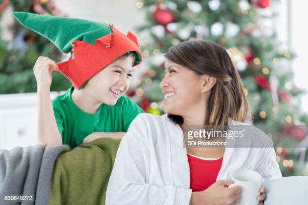 playful boy and his mom enjoy christmas morning - filipino christmas family stock pictures, royalty-free photos & images