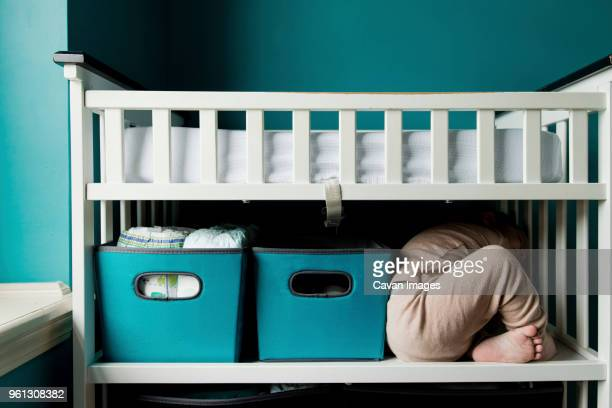 Playful boy hiding in bunkbed at home