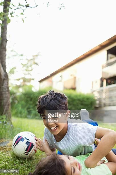 Playful boy lying at lawn against sky