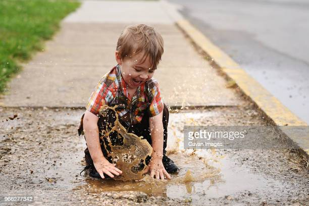 playful boy playing in puddle on footpath - mud stock pictures, royalty-free photos & images