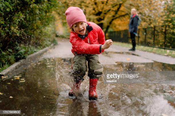playful boy splashing water in puddle on road - regen stockfoto's en -beelden