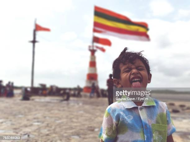 Playful Boy Sticking Out Tongue At Beach With Flag In Background Against Sky