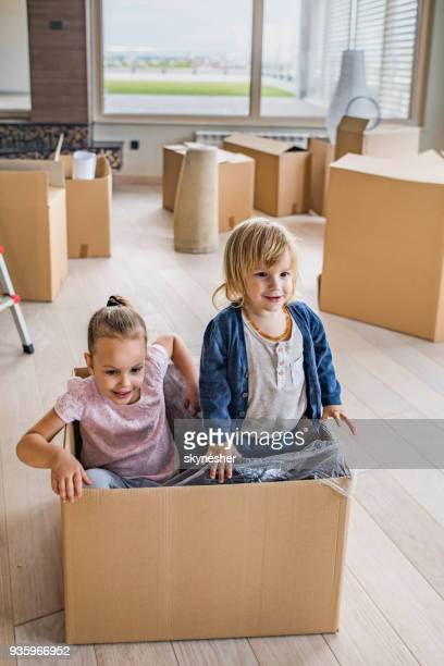 playful brother and sister relocating into new apartment and having fun in carton box. - penthouse girls stock pictures, royalty-free photos & images