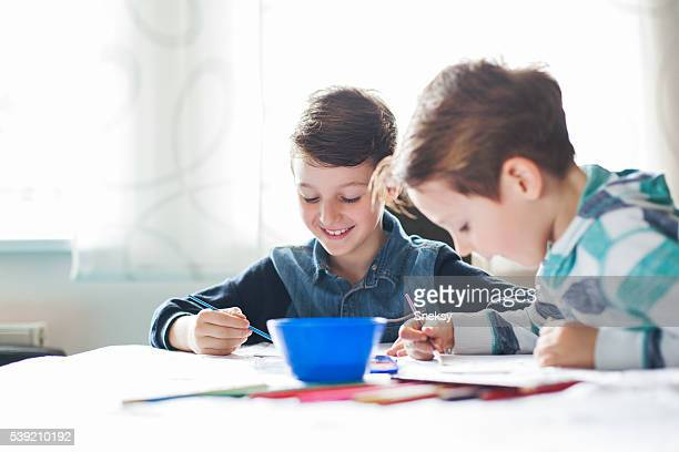 playful brothers painting together. - 8 9 jaar stockfoto's en -beelden