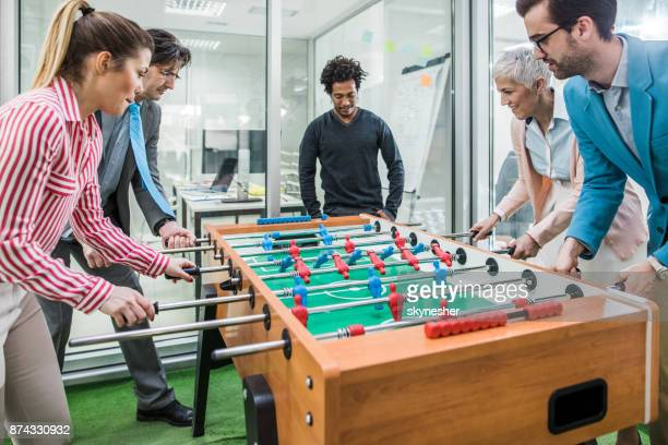 Playful business people having fun while playing foosball on a break in the office.