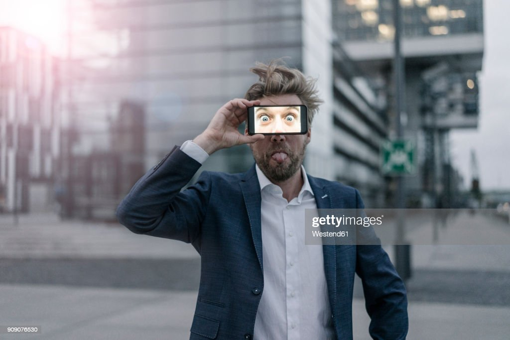 Playful businessman holding cell phone in front of his eyes : Stock-Foto
