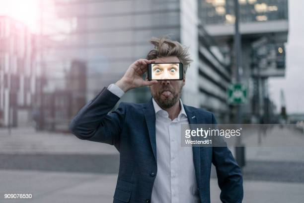 playful businessman holding cell phone in front of his eyes - respektlosigkeit stock-fotos und bilder
