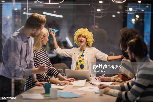 Playful businesswoman making a clown of herself on a meeting in the office.