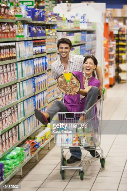 Playful Caucasian couple in grocery store