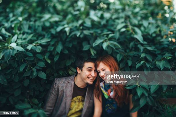 Playful Caucasian couple standing in leaves of tree