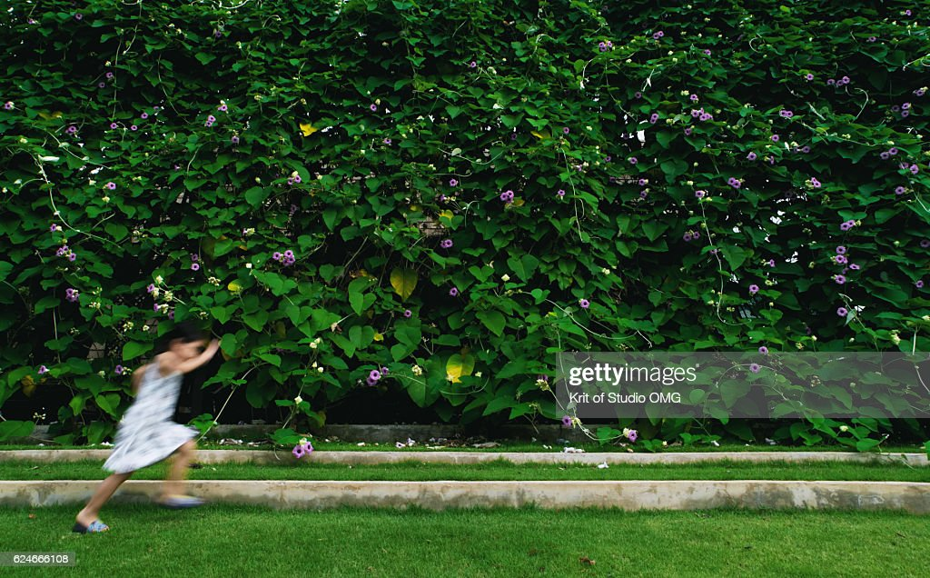 Playful child in front of green wall : Stock Photo