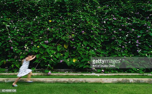 Playful child in front of green wall