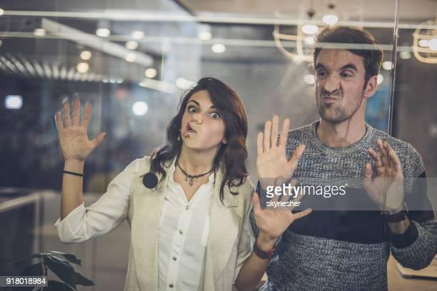 collègues ludiques s'amuser tout en collant leurs visages sur le mur de verre. - femme coquine photos et images de collection