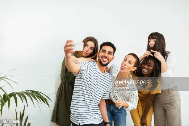 playful colleagues standing at brick wall taking a selfie - north african ethnicity stock pictures, royalty-free photos & images