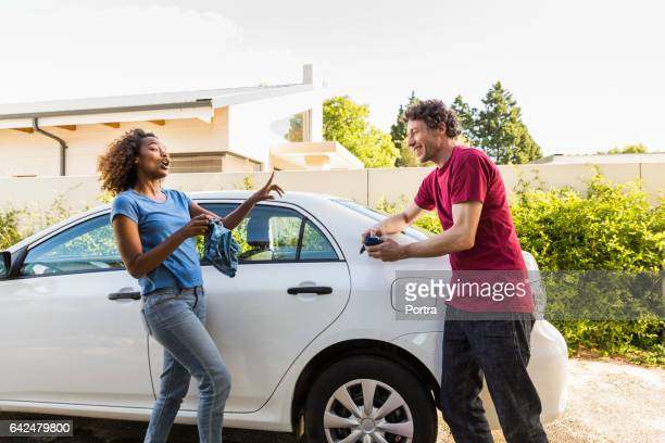 playful couple cleaning car at yard - couples showering stock pictures, royalty-free photos & images