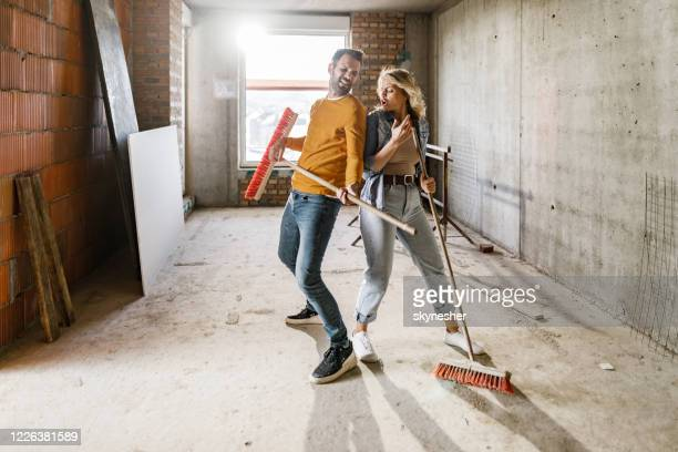 playful couple dancing and singing during home renovation process. - diy stock pictures, royalty-free photos & images