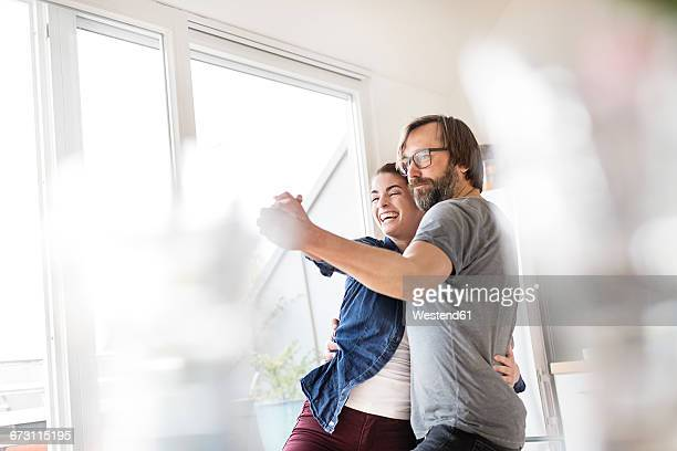 Playful couple dancing at home