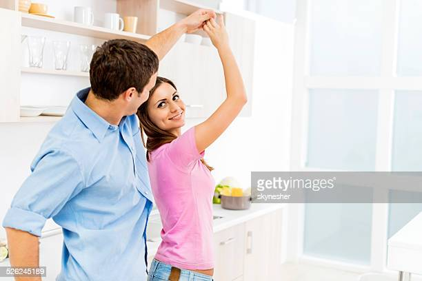Playful couple dancing in the kitchen.