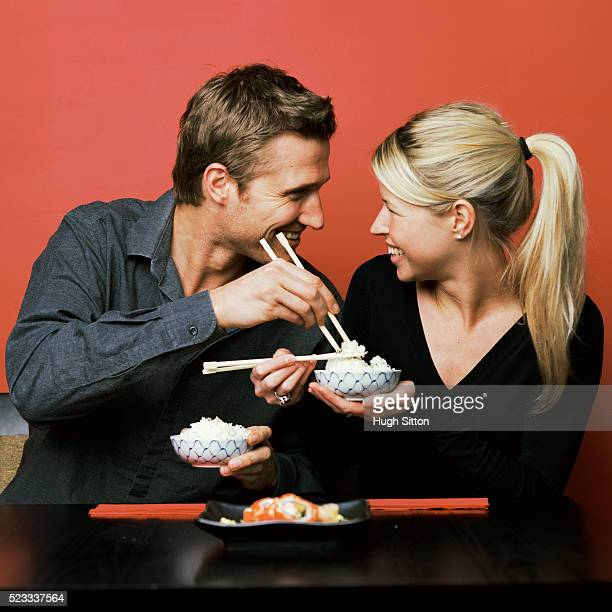 playful couple eating rice - hugh sitton stock pictures, royalty-free photos & images