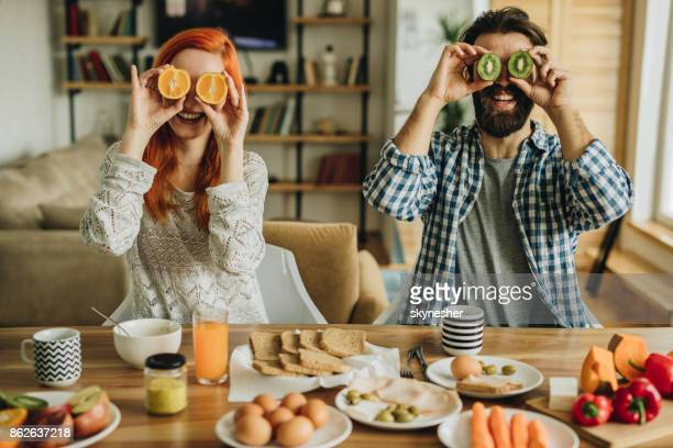 playful couple having fun during breakfast time at home. - orange fruit stock photos and pictures