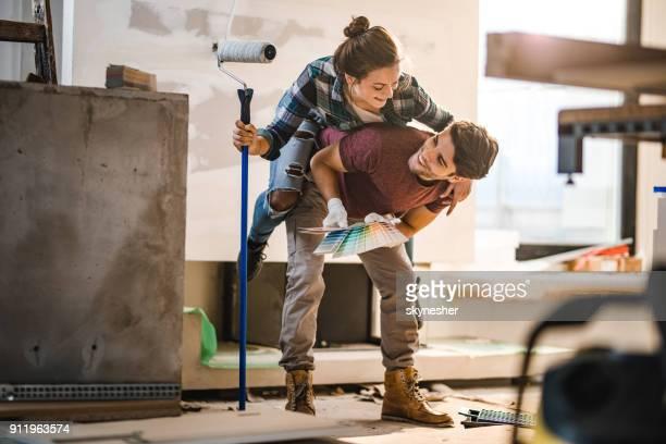 Verspielte Paare, die Spaß beim Huckepack während Renovierungs-Prozesses.