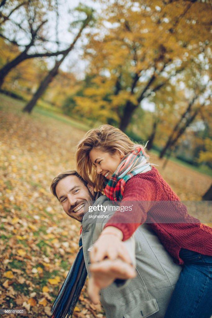 Verspielte Paare, die Spaß beim Huckepack im Herbst im Park. : Stock-Foto