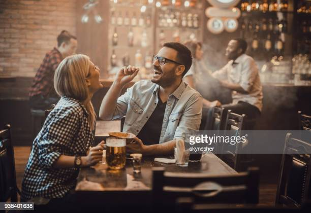 playful couple having fun with peanut during their night out in a pub. - pub stock pictures, royalty-free photos & images