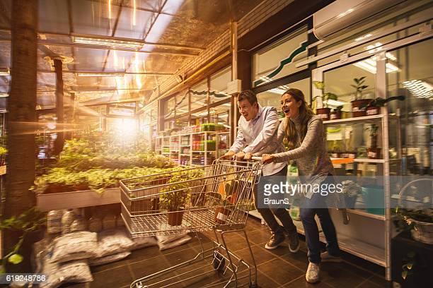 Playful couple having fun with shopping cart in garden center.