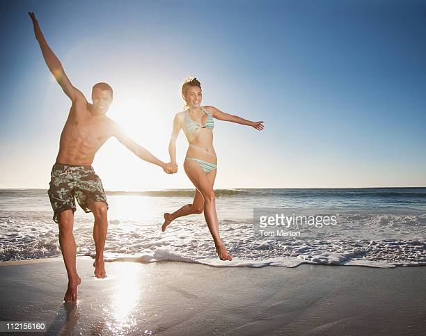 Playful couple holding hands and running on beach