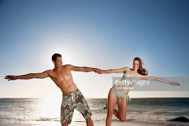 Joyeux couple tenant mains à la plage