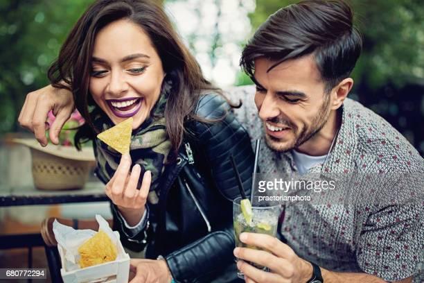 Verspieltes paar kämpft für Kartoffelchips in der bar