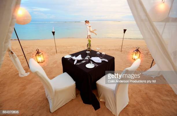 Playful couple near table prepared for romantic dinner at beach