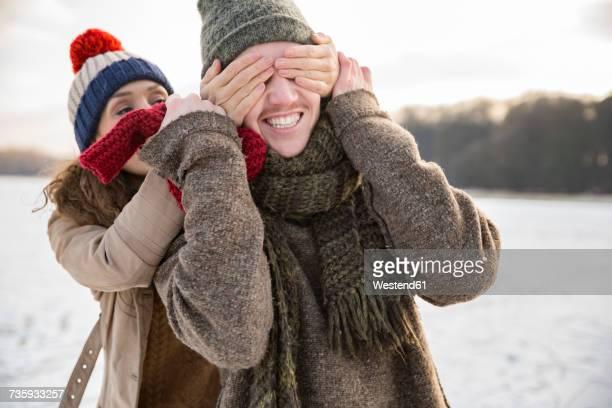 playful couple on frozen lake - augen zuhalten stock-fotos und bilder